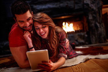 Young couple laying on floor and using tablet at home