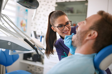 Dentist looking patient's teeth on dental clinic