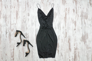 Little black dress and shoes. Wooden background, fashionable concept