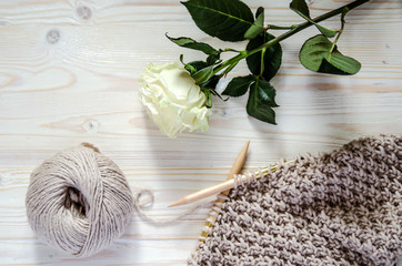 A horn of merino wool yarn, knitting on knitting needles and a white rose on a wooden surface.