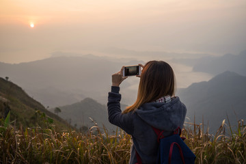 Young traveler taking photo beautiful landscape sunset