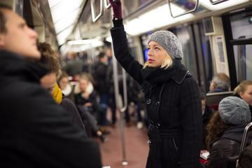 Beautiful blonde caucasian lady wearing winter coat traveling by metro in rush hour. Public transport.