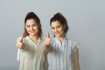 two beautiful smiling girl sisters twins in white blouses on a light background showing gestures success