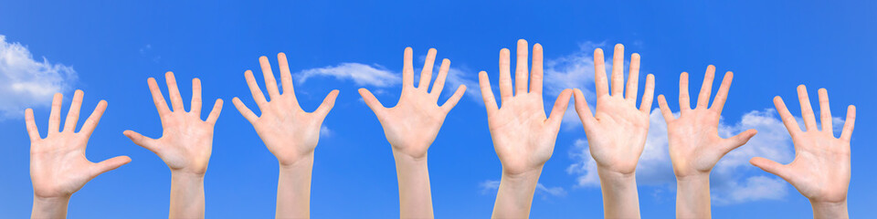 Group of caucasian white children is showing their hands with open palms on a  blue sky background in close-up ( high resolution).