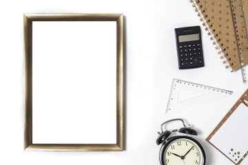 White desk top with gold empty frame for text or graphics, calculator, alarm clock, notebook, notebook and ruler