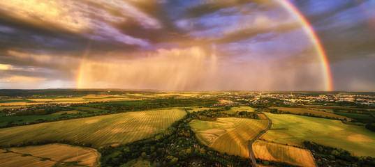 Panoramic, aerial view of a huge rainbow during a dramatic sunset over an agricultural landscape. Beautiful rainbow looking like a gate to the new world. Moravia, Czech landscape.
