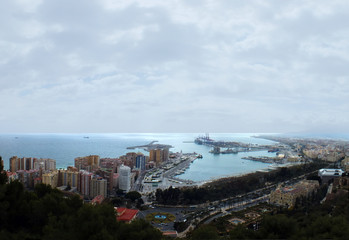 panoramic aerial image of malaga in spain showing the coast with port and docks with surrounding city hotels and ships out at sea
