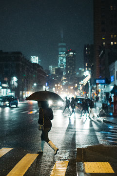 Woman crossing road with umbrella during rain at night