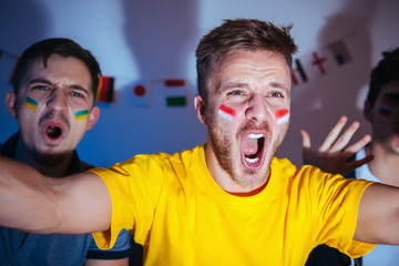 Exited football fan celebrating the goal with friends, watching match at home