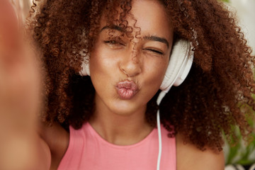 Close up shot of young pretty woman makes grimace as poses for selfie, enjoys recreation time, listens favourite playlist in website via big white headphones, uses modern device, has positive look