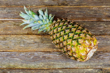 Detail of a organic pineapple on a wooden table.