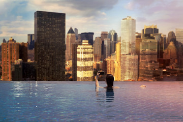 Young female in the pool on the roof on the background of skyscrapers of New York City, Manhattan