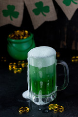 Saint Patrick's Day mug of green beer with green shamrocks and pot of gold in background