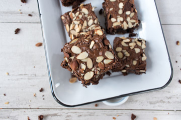 cut square Brownies with almonds on white baking pan
