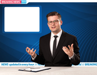 Television reporter telling breaking news at his studio desk with copy space