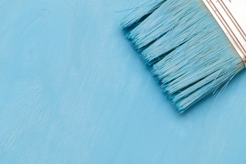 Staining the wooden surface with blue paint using a paint brush