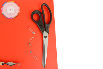 Tailoring scissors and pins on a red background. Free space for text.