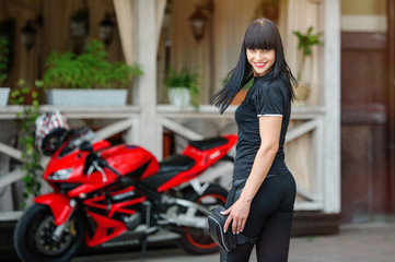 Girl biker in black clothes on a sports motorcycle posing in the city