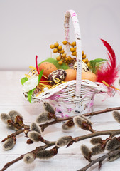 easter eggs in white basket with willow tree