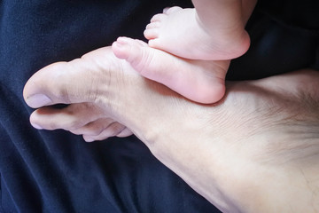 Father's foot with Baby feet,Foot father - son with similar characteristics.