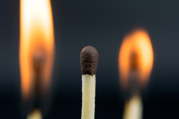 the flame of a burning match on a dark  blurred neutral background borrowed money concept, close up,  selective focus