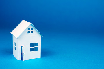 white small house on blue background, close up, selective focus Real Estate concept