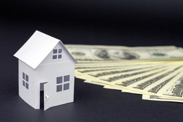 white small house and money bucks on blue background, Real Estate concept  close up, selective focus
