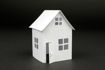 white small house on blurred dark background, close up, selective focus Real Estate concept