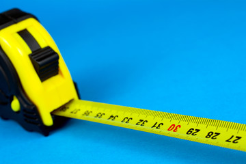 Self-retracting  yellow metal tape measure on a blue background selective focus close-up copy space