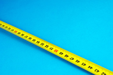 yellow Measuring tape on a blue background selective focus close-up copy space