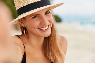 Restful delighted female with positive look makes selfie at exotic beach, poses against ocean view, spends unforgettable summer vacations, stands on tropical island. People and resort concept