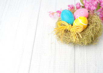 Happy Easter Eggs in nest with Pink flowers in top corner of framework on Rustic White Wash Painted Boards with empty or blank room or space for copy, text, your words. Horizontal shabby chic  flatlay