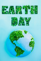 Creative concept with outline lettering Earth Day in green fresh grass sprouts and planet model on blue background. Save planet, nature. Earth Day, April 22. Space for text. Vertical.