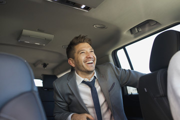 Young business man sitting in car service limousine
