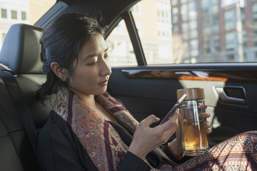 Businesswoman looking at smartphone while sitting in car