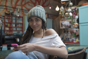 Portrait of a young woman sitting indoors and using smartphone