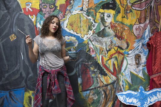 Portrait of young female artist standing in art studio