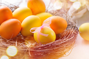 Fotoväggar - Easter colorful eggs in the nest. Beautiful painted, colorful yellow and orange color eggs with decorations on white wooden table background