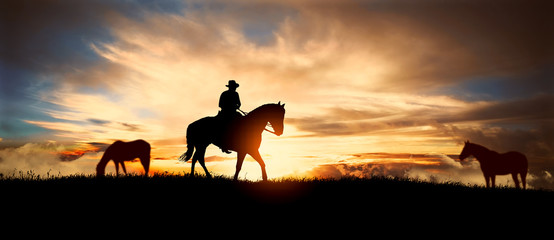Photo on textile frame Horseback riding A silhouette of a cowboy and horse at sunset