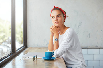 Thoughtful cute female blogger dressed in casual clothing, sits at coffe shop, contemplates about something as looks into window, uses laptop compuer, drinks hot beverage, has break after work