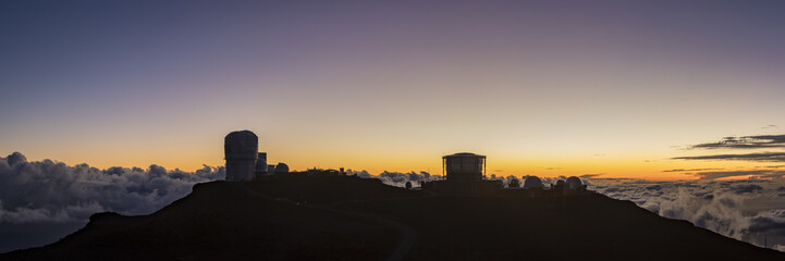 view from the summit of haleakala on the island of maui in hawaii in the pacific ocean showing the haleakala observatory against a stunning sunset and beautiful blue sky