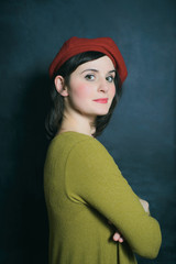 woman in red beret and green dress on the black wall background