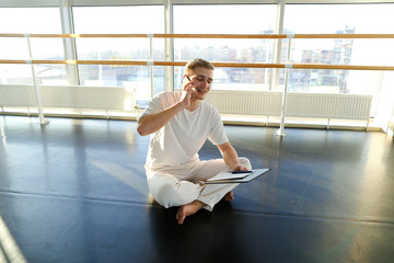 Fitness trainer discussing details with new client on smartphone in gym, handsome guy sitting on parquet floor with planchette in hands and talking on mobile. Male wearing sport clothes in spacious