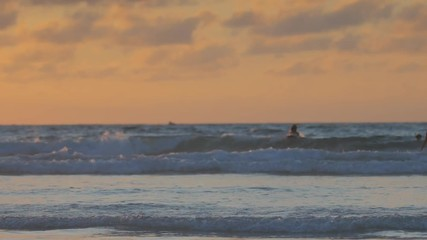 Wall Mural - Sunset sea, tropical beach, two girls running out into the water with joy making splashes in slowmotion