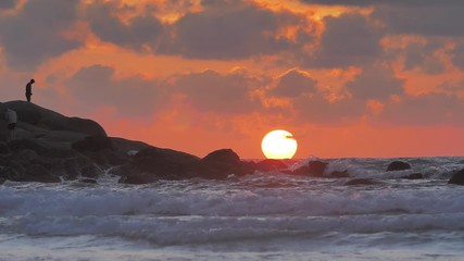 Wall Mural - Beautiful Ocean sunset with last light of the Sun in sea waves crashing against rocks in slowmotion