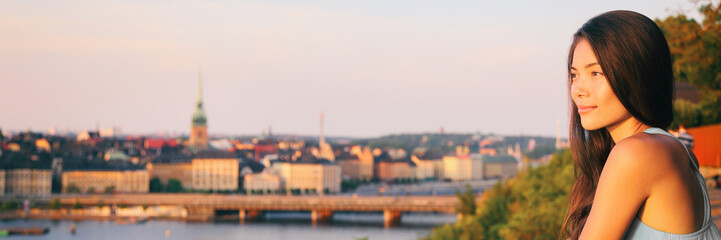 Wall Mural - Europe travel Sweden tourist Asian woman looking at Stockholm old town landscape banner watching sunset from Monteliusvagen overlooking Gamla Stan, the old town. Sweden. Scandinavian summer vacation.