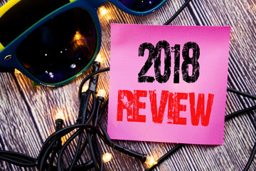 Hand writing text caption showing 2018 Review. Business concept for Feedback On Progress written sticky note empty paper background with copy space with sunglasses