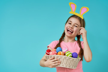 Girl holding basket with painted eggs