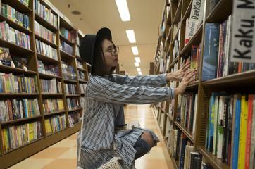 次に読む本を悩みながら探す美人女子大学生。