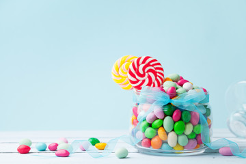 Jar staffed sweet colorful candy against turquoise background. Gifts for Birthday party.